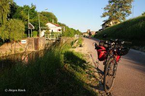 Fahrrad mit roten Packtaschen auf dem Kanalradweg. Sonne wirft lange Schatten.