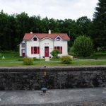Schleusenhaus 16 am Saar-Kohlekanal. Weiß mit roten Fenstern und Tür, Ziegeldach.
