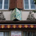 Zwei Sandsteinfiguren, dazwischen ein Schild mit der Aufschrift 'Fleurs'.