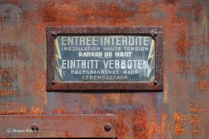 Verrostetes zweisprachiges Emaille-Verbotenschild an einer Trafostation.