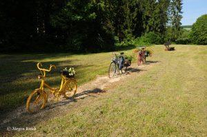 Drei bunte bemalte Fahrräder und eine Parkbank an einem Picknick-Platz