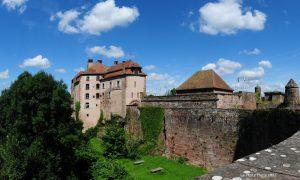 Eine mittelalterliche Spornburg unter blauem Himmel und über grünem Gras