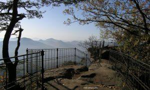 Hinter einem Eisengeländer unter Zweigen sieht man weit über graublaue Hügel.