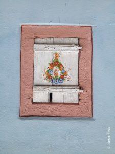 Ein geschlossener, weißer Fensterladen mit rosa bemaltem Sandsteingewänd. Ehemals ein Viehstall womöglich. Der Laden ist mit Blümchen bemalt.