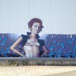 Ein Mädchen als kunstvolles Graffiti stützt die Arme in die Hüfte. Hintergrund türkis-graublaue Verzierung an kahler Betonwand