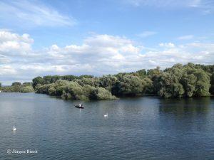 Graublauer Fluss in der unteren Bildhälfte, oben blauer Himmel und leichte Wolken, dazwischen viel Grün.
