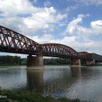 Fachwerk-Eisenbahnbrücke über den Rhein, Bogen, graublauer Himmel, der Fluss. Rostbraun