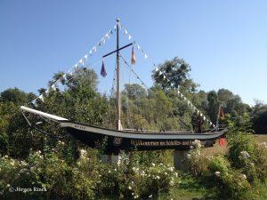 Schlankes, schwarzes Schiff mit Mast und Fähnchen, aufgestellt im Grünen als Dekoration