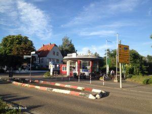 Über die Straße und eine Verkehrsinsel geblickt sieht man ein ovales Gebäude, Bäume und blauen Himmel